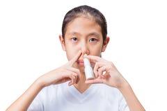 Adolescente che per mezzo dello spray nasale, fondo bianco Fotografie Stock Libere da Diritti