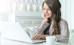 Adolescente che per mezzo di un computer portatile Immagine Stock