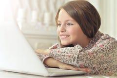 Adolescente che per mezzo di un computer portatile Immagini Stock