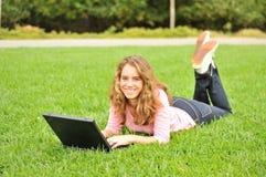 Adolescente che pone sull'erba con un computer portatile Fotografia Stock