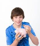 Adolescente che riempie il suo porcellino salvadanaio Fotografia Stock