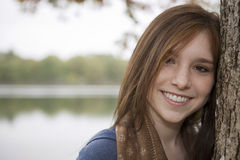 Adolescente che si appoggia su un albero vicino ad un lago Immagine Stock Libera da Diritti