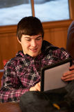 Adolescente che si distende sul sofà con il calcolatore del ridurre in pani Immagine Stock Libera da Diritti