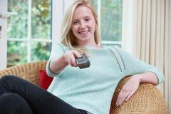 Adolescente che si rilassa e che guarda TV a casa fotografia stock libera da diritti
