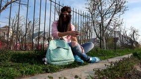 Adolescente che si siede all'aperto vicino al recinto del metallo e video d archivio