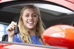 Adolescente che si siede in automobile, tenente i tasti dell'automobile Fotografia Stock Libera da Diritti