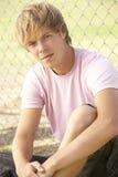 Adolescente che si siede nel campo da giuoco Immagine Stock