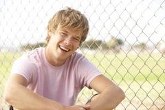 Adolescente che si siede nel campo da giuoco Fotografia Stock Libera da Diritti