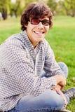 Adolescente che si siede nel parco Fotografie Stock