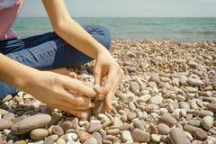 Adolescente che si siede su un ciottolo La mano ha messo una pietra sulla stenditura delle pietre sulla riva del mare blu fotografie stock