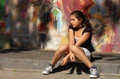 Adolescente che si siede su un marciapiede Fotografie Stock Libere da Diritti