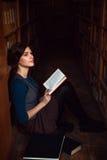 Adolescente che si siede su un pavimento della biblioteca e colto Immagine Stock