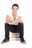 Adolescente che si siede sul mucchio dei libri Fotografia Stock
