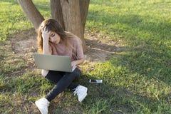 Adolescente che si siede sul prato inglese con un computer portatile Fotografia Stock