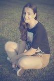 Adolescente che si siede sull'erba Fotografia Stock Libera da Diritti