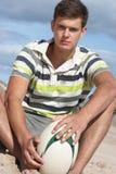 Adolescente che si siede sulla sfera di rugby della holding della spiaggia immagine stock