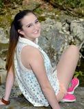 Adolescente che si siede sulle rocce immagini stock