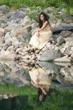 Adolescente che si siede sulle rocce dallo stagno Fotografia Stock Libera da Diritti