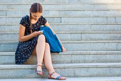Adolescente che si siede sulle scale e che guarda in telefono Fotografia Stock