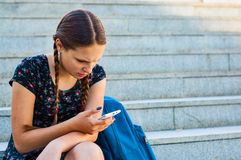 Adolescente che si siede sulle scale e sulle tenute uno smartphone Fotografie Stock Libere da Diritti