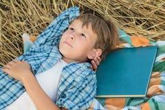 Adolescente che si trova e che sogna ispirato dal libro Fotografia Stock