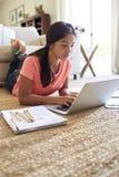 Adolescente che si trova sul pavimento nel salone che fa il suo compito facendo uso di un computer portatile, angolo basso, fine  immagine stock