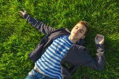 Adolescente che si trova sull'erba con il telefono fotografie stock