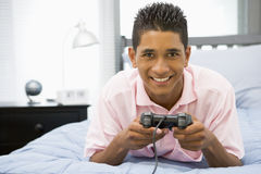 Adolescente che si trova sulla base che gioca video gioco Immagini Stock