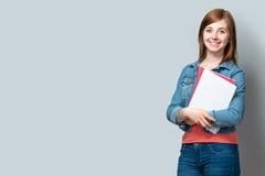 Adolescente che sta con i libri Fotografia Stock