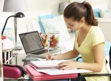 Adolescente che studia allo scrittorio in camera da letto Immagine Stock Libera da Diritti