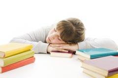 Adolescente che studia allo scrittorio che è faticoso. Immagine Stock
