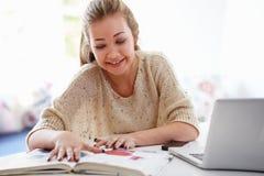 Adolescente che studia sul computer portatile a casa Immagine Stock