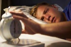 Adolescente che sveglia a letto e che spegne sveglia Immagini Stock Libere da Diritti