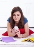 Adolescente che texting invece di imparare Fotografia Stock Libera da Diritti