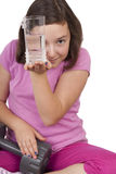 Adolescente che tiene bicchiere d'acqua e peso Immagine Stock Libera da Diritti