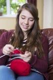 Adolescente che tricotta a casa Fotografie Stock Libere da Diritti