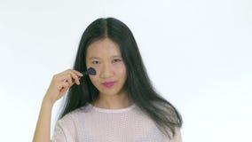 Adolescente chino que aplica maquillaje con el cepillo almacen de video