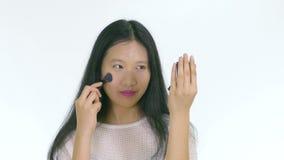 Adolescente chino que aplica maquillaje con el cepillo almacen de metraje de vídeo