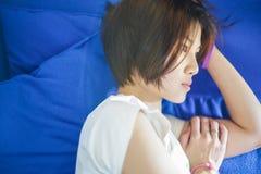 Adolescente chino que toma una siesta en un sofá púrpura Imágenes de archivo libres de regalías