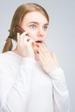 Adolescente chocado que habla en el teléfono móvil. aislado Foto de archivo