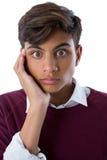 Adolescente chocado que se opone al fondo blanco Foto de archivo