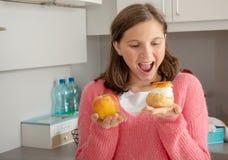 Adolescente choisie avec la pâtisserie douce et la pomme organique images libres de droits