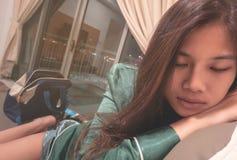 Adolescente cinese che prende un pelo su un sofà Fotografia Stock Libera da Diritti