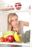Adolescente com fruta no refrigerador imagens de stock royalty free
