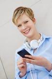 Adolescente com smartphone e fones de ouvido Fotografia de Stock Royalty Free