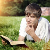 Adolescente com um livro exterior Fotos de Stock Royalty Free