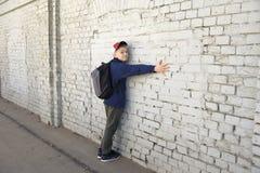 Adolescente com um olhar pensativo Parede de tijolo do fundo fotografia de stock