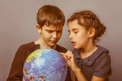 Adolescente com uma menina que olha um globo Fotos de Stock Royalty Free