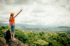 Adolescente com uma trouxa que está em uma parte superior da montanha Fotografia de Stock Royalty Free