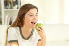 Adolescente comiendo una manzana en un sofá en casa Imagen de archivo libre de regalías